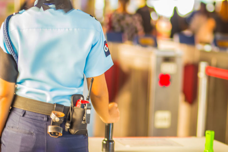 Midsection Of Female Security Guard Standing At Airport