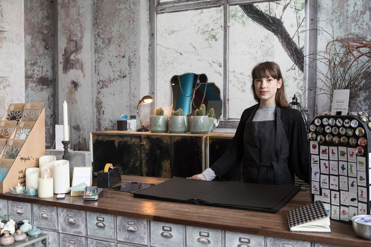 Portrait of a young woman standing in restaurant