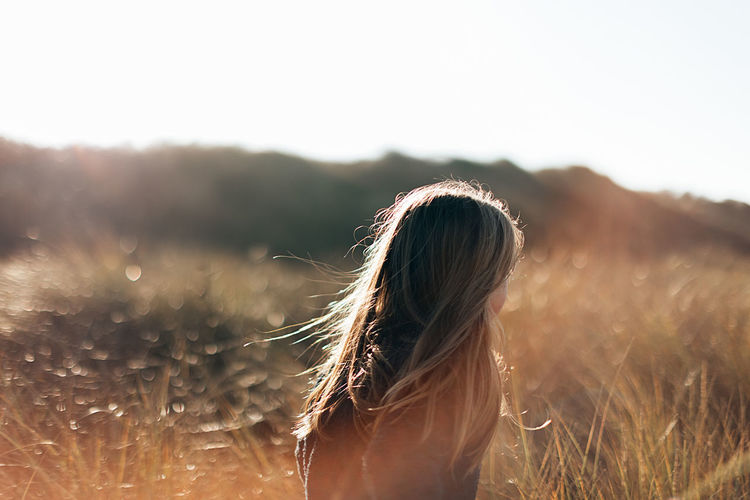 Back view of a young girl with long hair running in a meadow at sunset