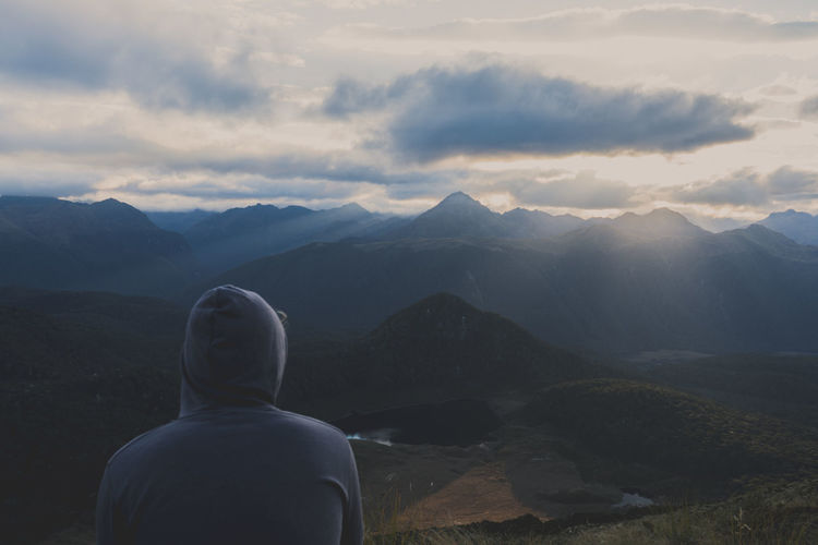 Rear view of man looking at mountains against cloudy sky