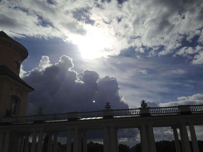 Low angle view of silhouette bridge against sky and building