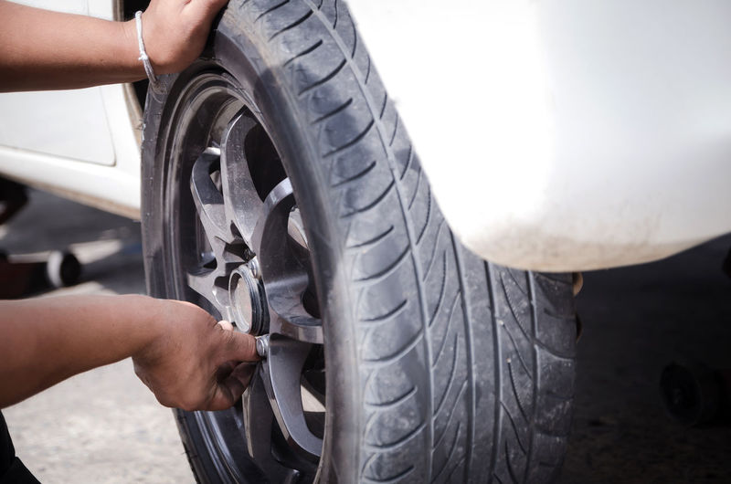 Adult Adults Only Auto Repair Shop Car Close-up Day Human Body Part Human Hand Land Vehicle Men Mode Of Transport Occupation Off-road Vehicle One Person Outdoors People Real People Tire Transportation Wheel