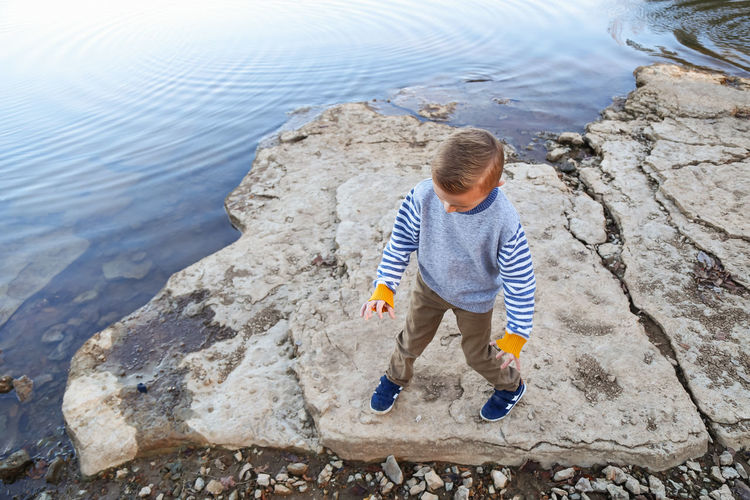 Young Boy Picking Up Rock To Throw Into Lake Childhood Child Water Full Length One Person Boys Casual Clothing Males  Leisure Activity High Angle View Nature Day Outdoors Rock - Object Autumn Fall Lake Throwing Rocks Boy Childhood Memories Little Girl Young Boy Young Child Autumn colors Sweater