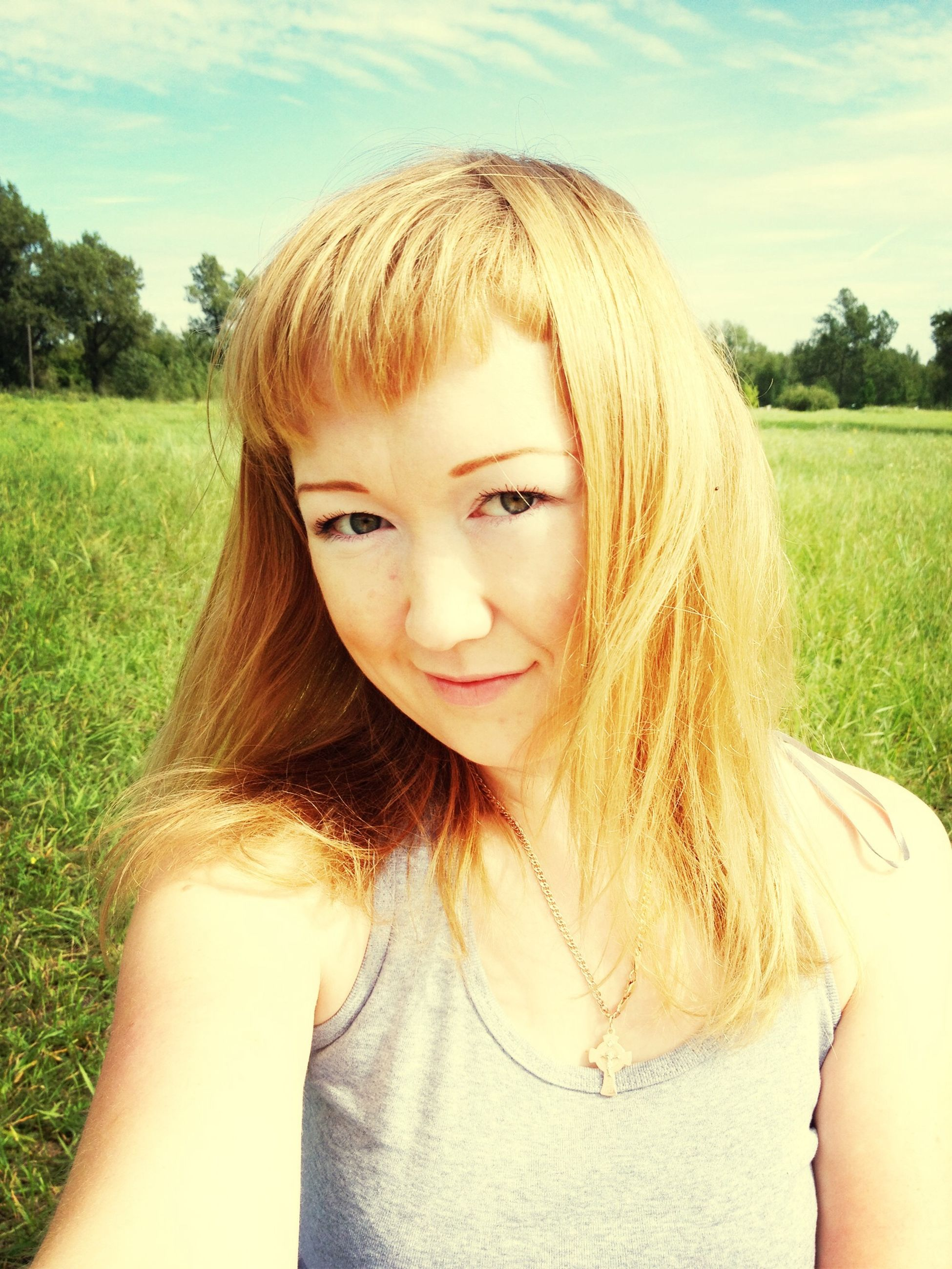 person, grass, young women, lifestyles, long hair, headshot, leisure activity, portrait, young adult, field, looking at camera, blond hair, tree, brown hair, smiling, grassy, sunlight