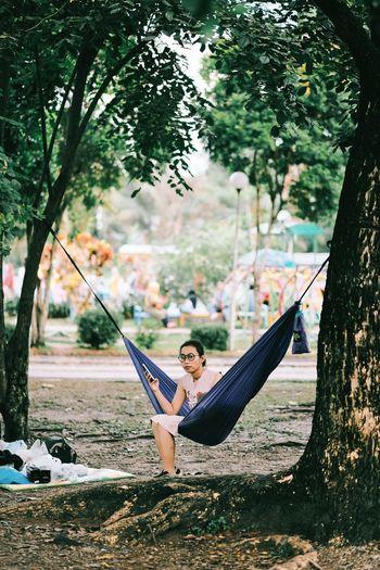 Man sitting on hammock by tree