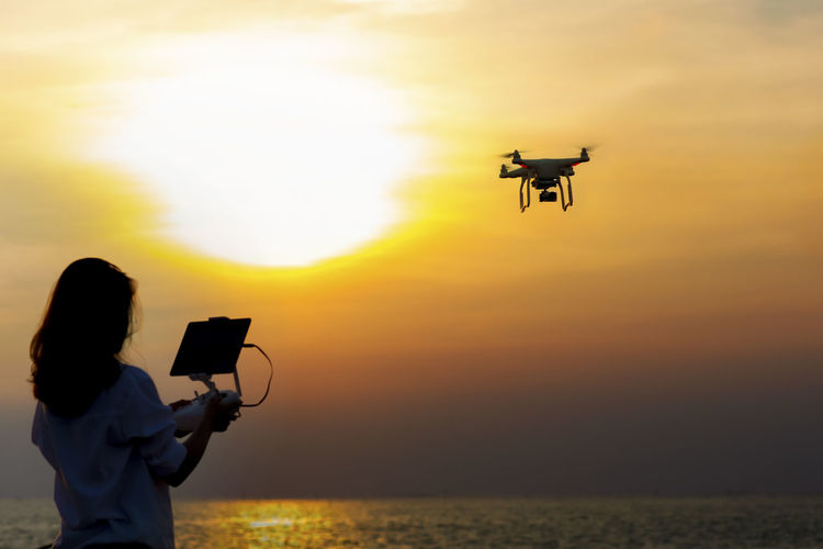 Woman flying drone over sea against sky during sunset