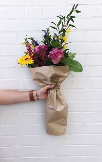Cropped image of hand holding bouquet against wall