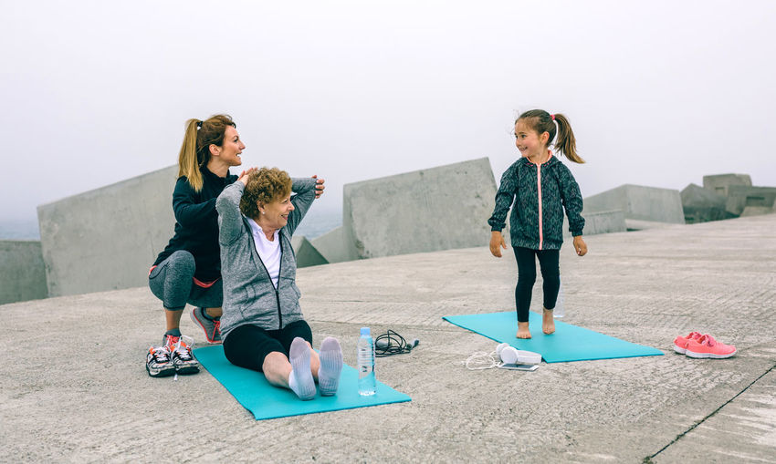 Young woman training girl and senior woman by sea pier Exercising Happiness Happy Horizontal Modern Pier Trainer Vitality Woman Active Caucasian Female Fitness Girl Healthy Lifestyles Mature Women Outdoors People Real People Sea Sport Sportswear Stretching Three People