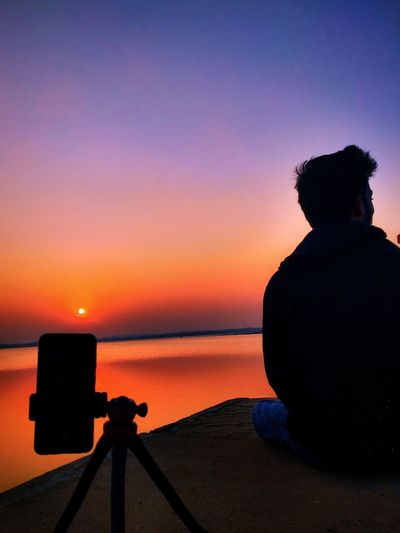 Silhouette person sitting against sky during sunset