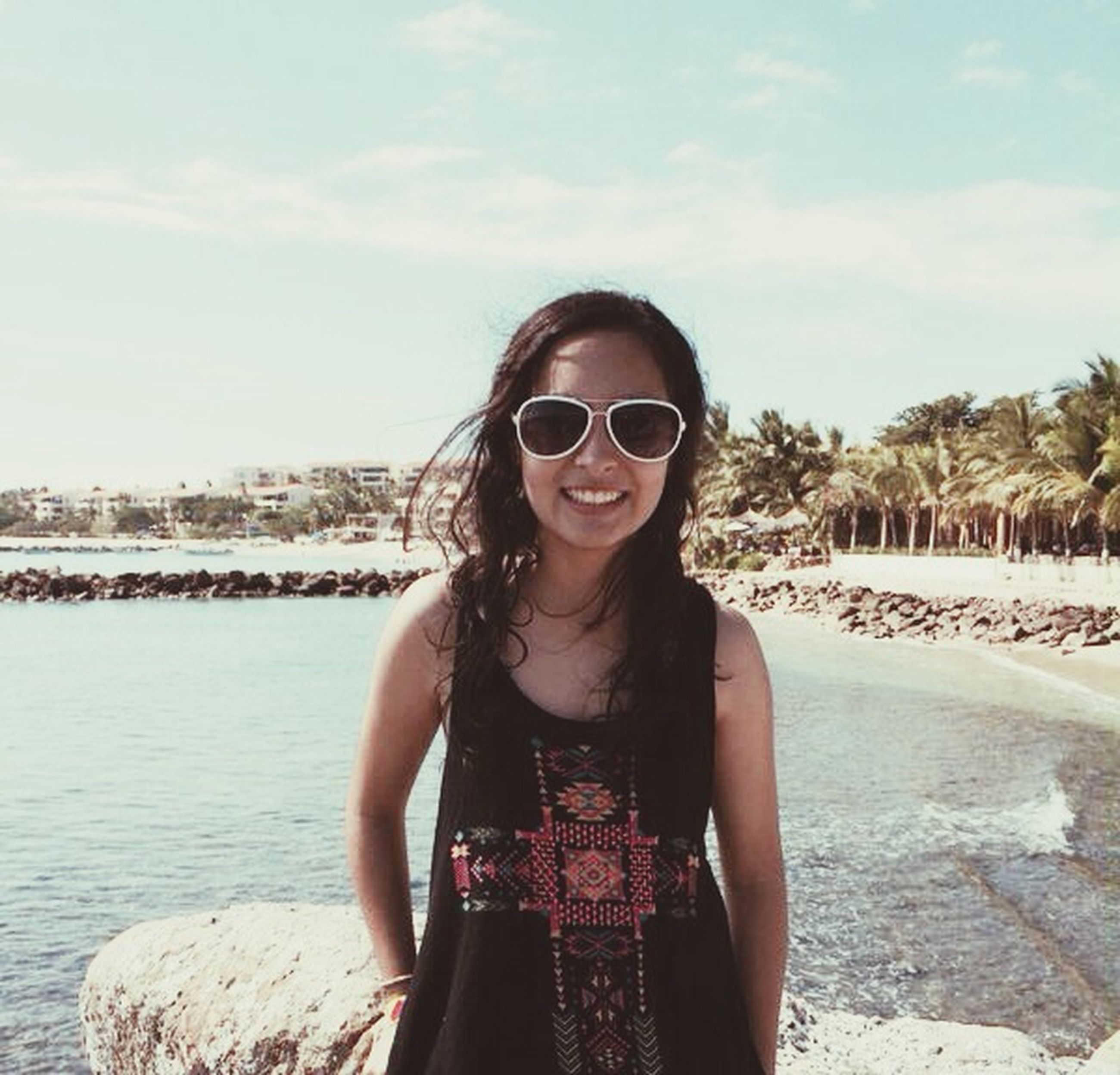 portrait, young adult, looking at camera, lifestyles, sunglasses, person, front view, leisure activity, casual clothing, young women, smiling, standing, water, sky, happiness, toothy smile, beach