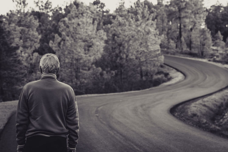Rear view of senior man standing on road against trees in forest