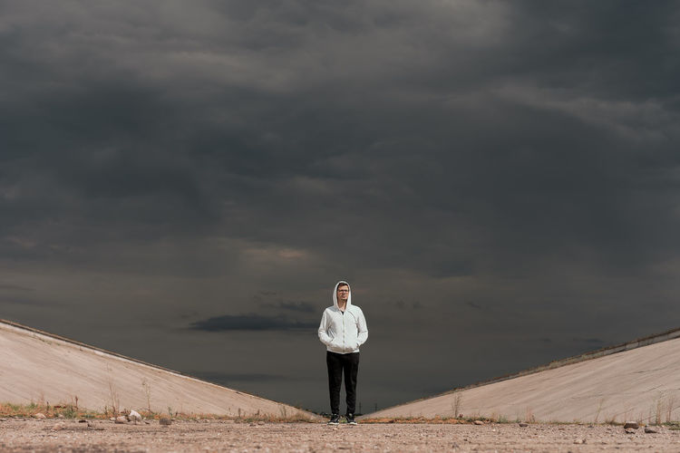 Portrait of young man wearing hooded shirt standing on field against cloudy sky