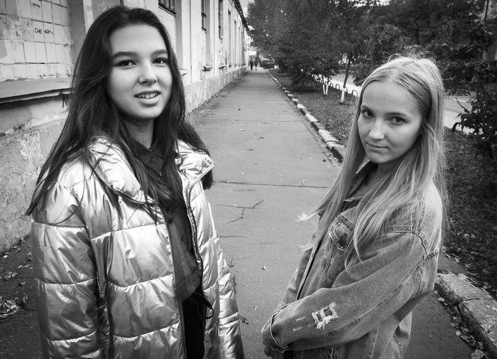 Portrait of female friends standing on sidewalk