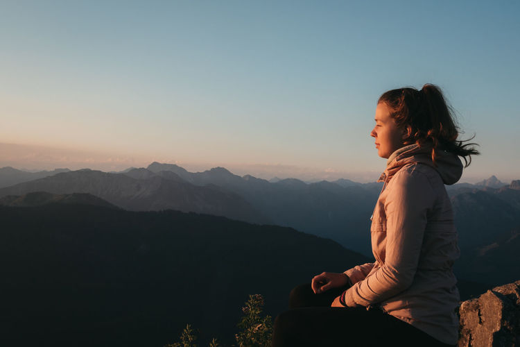 Woman sitting on mountain against sky during sunrise