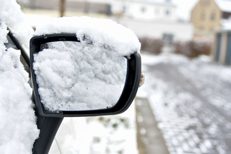 Close-up of snow covered car on side-view mirror