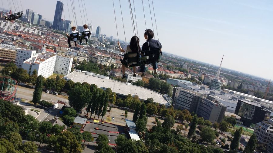 People on chain swing ride over buildings in city