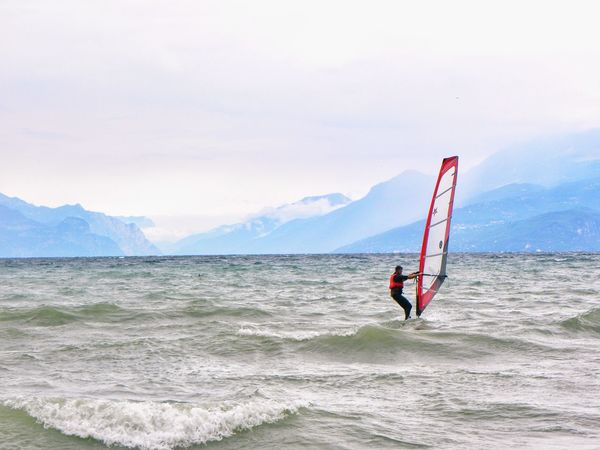 Adults Only Sport Adventure Sportsman Leisure Activity Sky Day Sports Clothing Skill  Outdoors Windsurfing Agility Extreme Sports Landscape Enjoying Nature Holidays Wave Looking At The Sea Vacations Tranquility Scenics Mountains Lago Di Garda Beauty In Nature Athleticism