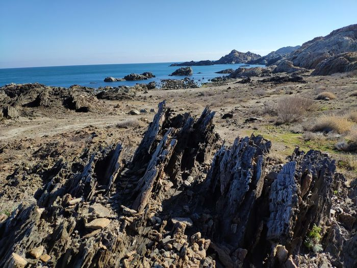 Panoramic view of rocks on beach against clear sky