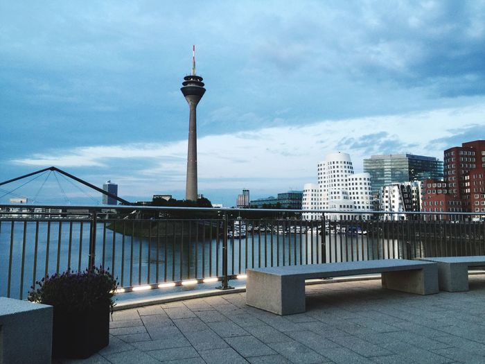 Rheinturm tower by rhine river in city against cloudy sky