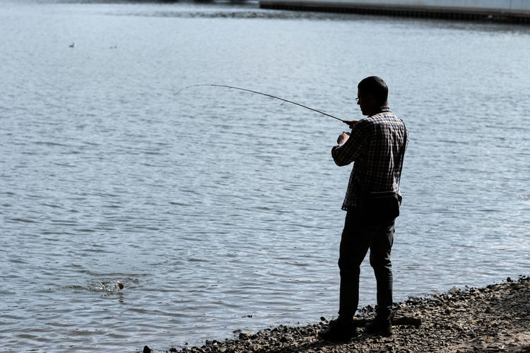 Rear view of man fishing at lakeshore