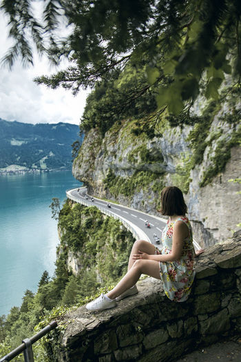 Side view of woman sitting on retaining wall over road by lake