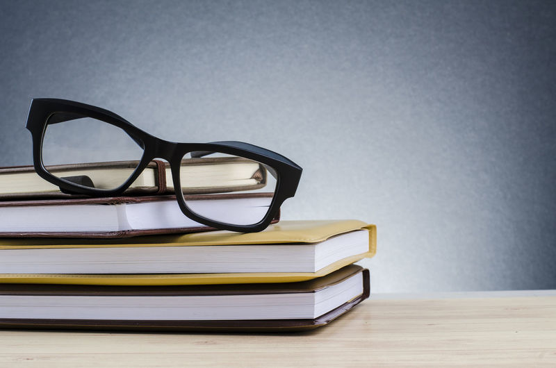spectacles on stack of books over beautiful gradient background with reverberation Glasses Eyeglasses  Table Indoors  Publication Still Life Book No People Education Close-up Absence Stack Fashion Wood - Material Studio Shot Furniture Copy Space Simplicity Eyesight Personal Accessory Reading Glasses
