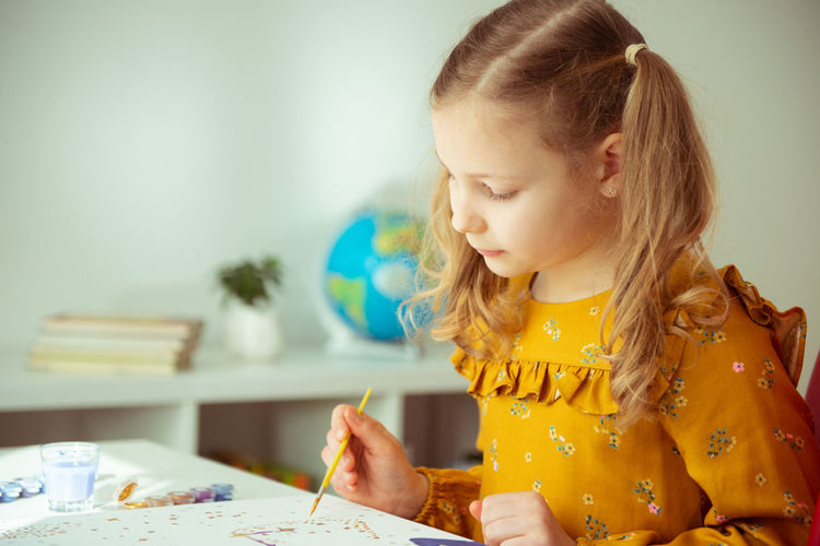 Cute girl painting while sitting at home