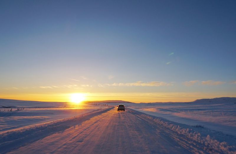 Driving Icy Road Beauty In Nature Cold Temperature Day Full Length Landscape Nature One Person Outdoors People Polar  Real People Road Scenics Sky Snow Sun Sunlight Sunset The Way Forward Tranquil Scene Tranquility Transportation Travel Destinations Vacations Winter