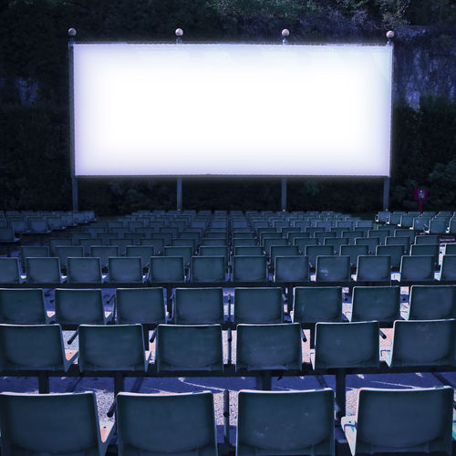 Empty chairs against projection screen