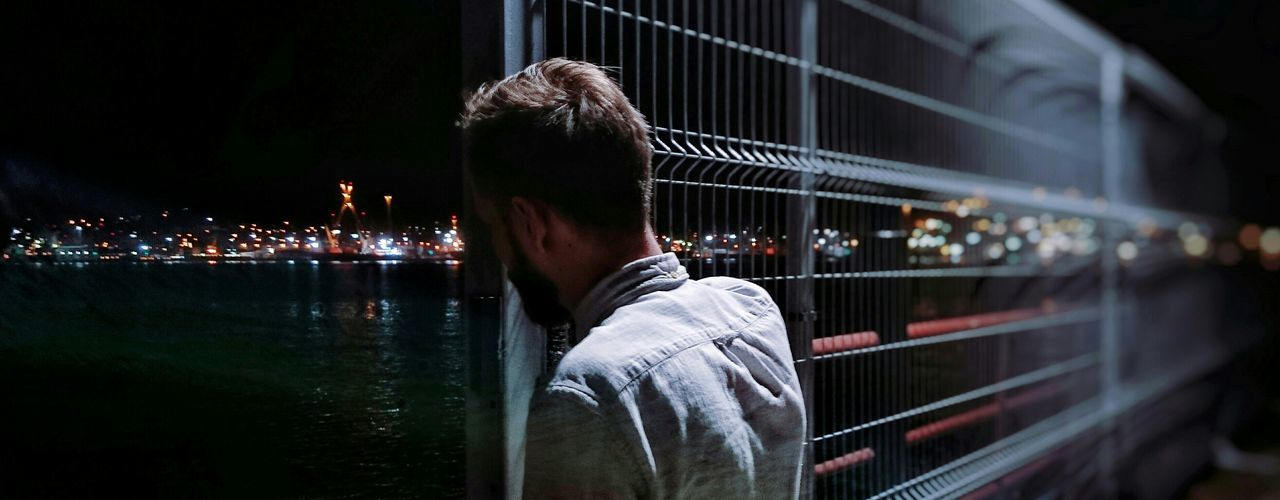 Panoramic view of man standing by metallic fence on pier at night