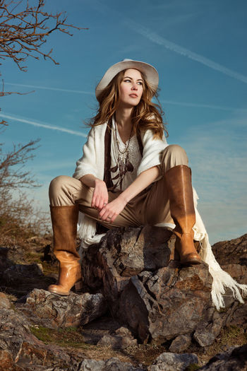Fashionable young woman sitting on rock against sky