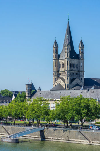 Close-up of the the Great Saint Martin Church in Cologne / Germany 2018. Height: 50 meters Style: romanesque architecture Built: in the 10/11st century Great Saint Martin Church Cathedral Church Cologne Sunlight Tourist Attraction  Travel Photography Trees Architecture Blue Building City Day Europe Germany Nature Religion River Saint Martin Church Sky Spire  Sunshine Tower Travel Destinations Water