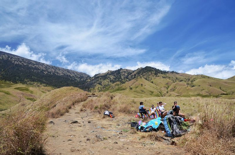 MOUNT RINJANI, LOMBOK INDONESIA. SEPT 16th 2017- Group of tourist take a rest before continue their journey to Mount Rinjani via sembalun route. Good weather with amazing blue sky. INDONESIA Mount Rinjani Sembalun Route Rest Eat Drink Wallpaper Background Hiking Hikingadventures Women Men Togetherness Sky Landscape Cloud - Sky Hiker Hiking Pole Backpack Mountain Climbing