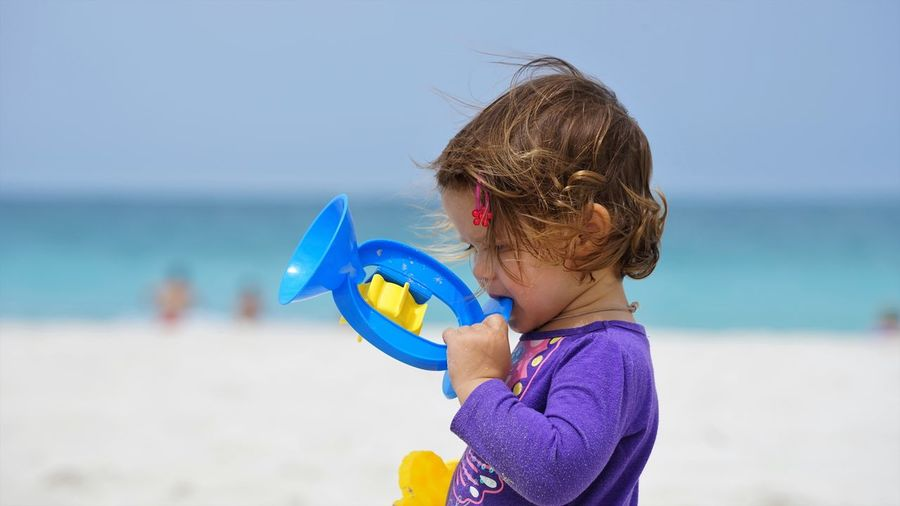 Cute girl holding toy while playing at beach against sky