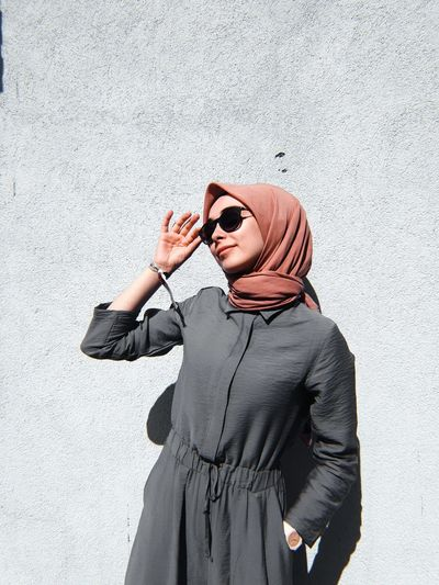 Young woman looking away while wearing sunglasses standing against wall
