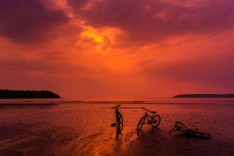 Cycle Beach Beauty In Nature Day Horizon Over Water Nature Orange Color Outdoors Sand Scenics Sea Silhouette Sky Standing Sunset Tranquility Two People Water