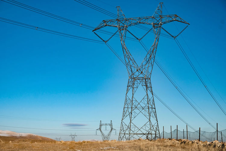Low angle view of electricity pylon on field against clear sky