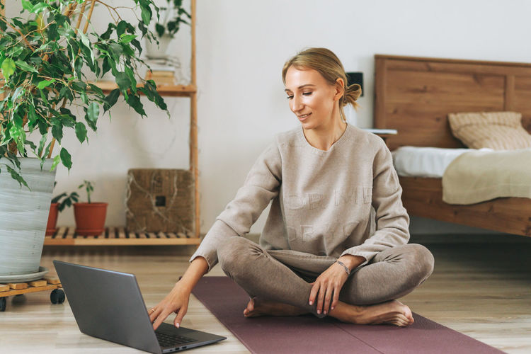 Beautiful blonde young woman in comfortable sport wear practice yoga in cozy bedroom at home