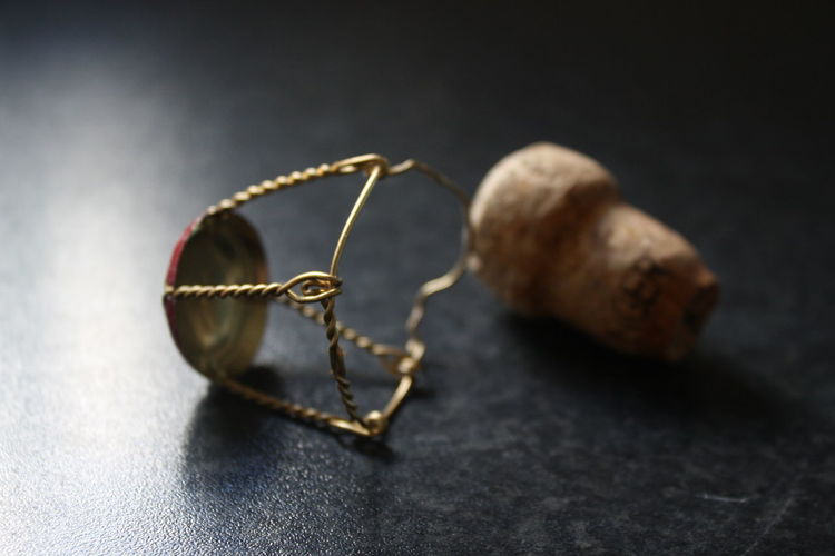 Close-Up Of Champagne Cork And Muselet On Table