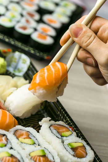 Cropped hand having sushi and sashimi in box on table