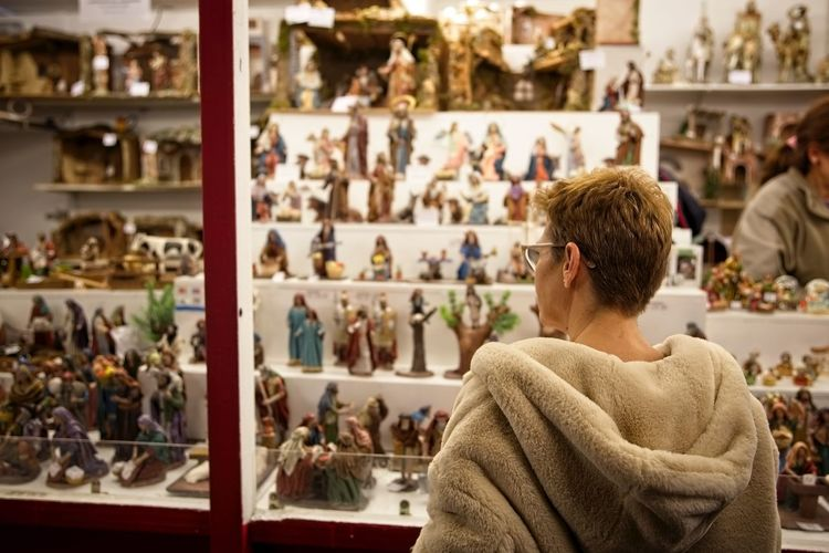 Rear View Of Woman Buying Figurines At Market During Night