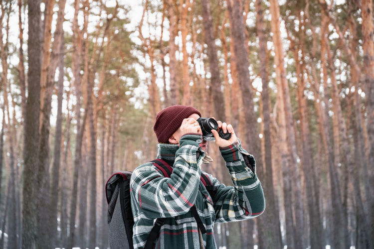Man photographing while standing in forest during winter