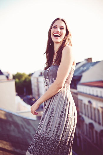 Happy woman laughing on rooftop