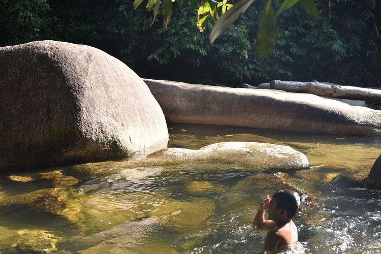 Full length of woman on rocks at shore