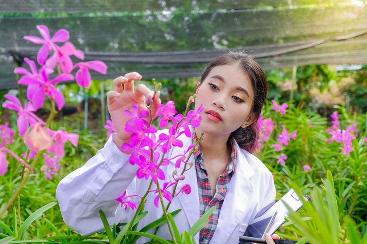Portrait of woman on pink flowering plants