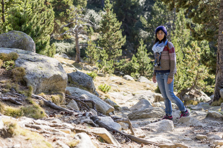 Young woman standing on rock against trees