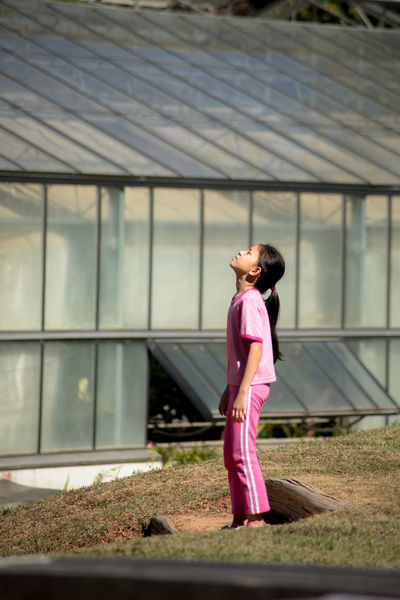 Little girl face up to breathe fresh air Architecture Breathe Built Structure Casual Clothing Clothing Day Face Up Full Length Girl Leisure Activity Lifestyles Nature Outdoors Pink Color Plant Side View Standing Women