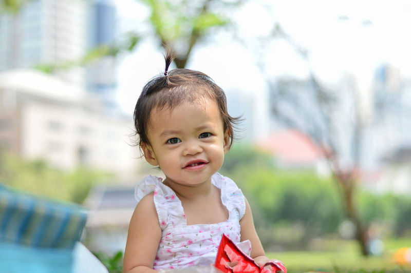 Asian baby girl she is smile. Asian  Girl Smiling Thailand Park Baby Child Sitting