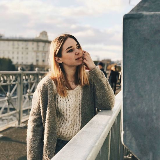 Young Woman Standing By Railing Against Sky