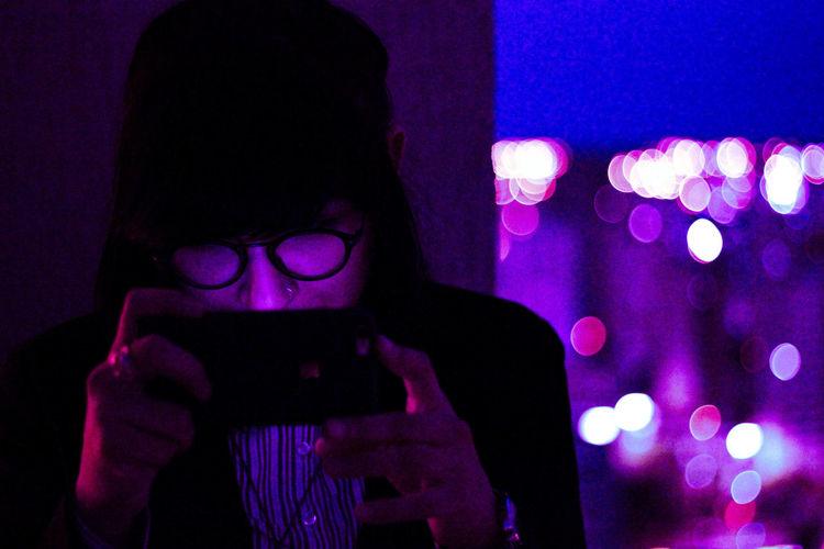 Portrait of man using smart phone at night